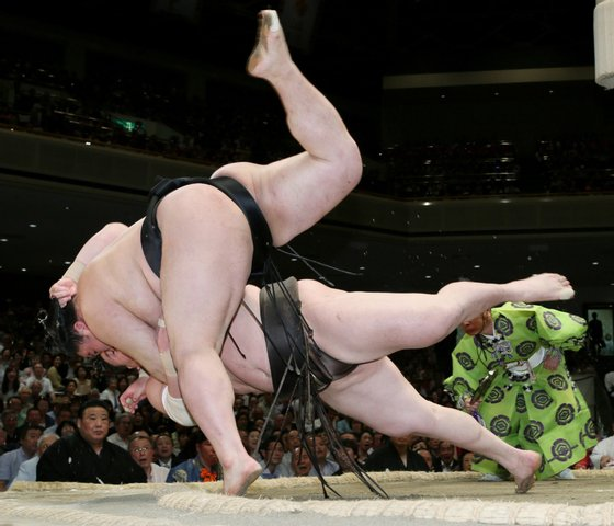 Sumo grand champion Hakuho (top) is thrown by champion Goeido on the 12th day bout of the Summer Grand Sumo Tournament in Tokyo on May 21, 2015. Hakuho lost the match but still leads the 15-day tournament 10-2. AFP PHOTO / JIJI PRESS JAPAN OUT (Photo credit should read JIJI PRESS/AFP/Getty Images)