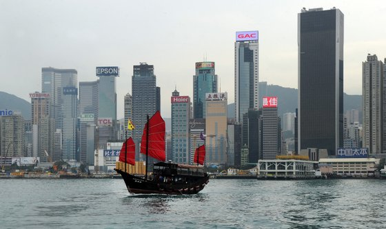 This photo taken on March 13, 2014 shows the Aqua Luna, one of Hong Kongs last remaining traditional Chinese junks, sailing past Hong Kong's skyline. Hong Kong's economy is expected to expand at its fastest pace in three years in 2014, the government said on February 26, while slashing public welfare spending as it cautioned over global economic headwinds and projected a narrowing budget surplus. AFP PHOTO / Laurent FIEVET (Photo credit should read LAURENT FIEVET/AFP/Getty Images)