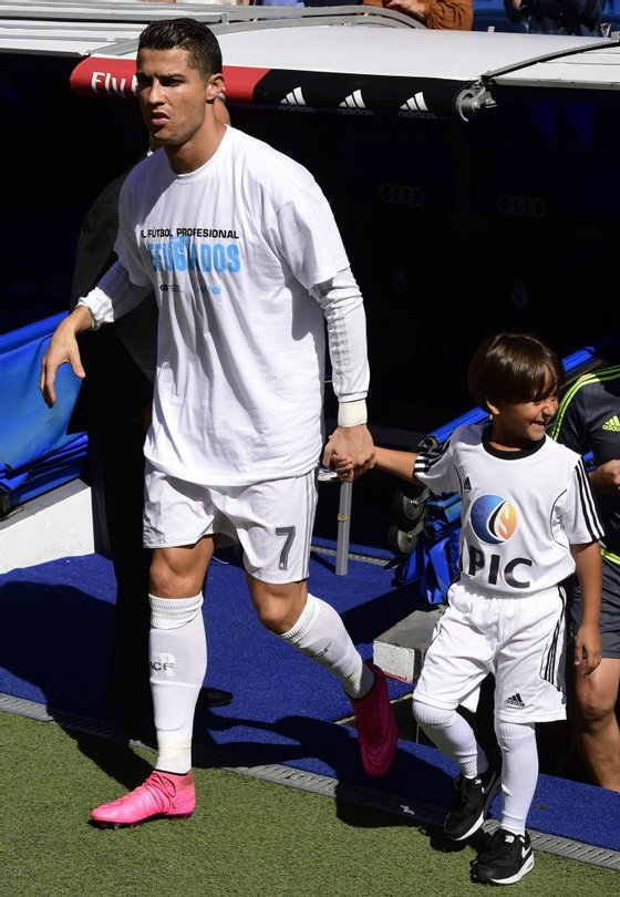 Real Madrid's Portuguese forward Cristiano Ronaldo (L) enters the pitch with Zaid, son of Osama Abdul Mohsen (C), the Syrian refugee who made world headlines when a Hungarian journalist tripped him over as he fled, before the Spanish league football match Real Madrid CF vs Granada FC at the Santiago Bernabeu stadium in Madrid on Spetember 19, 2015. AFP PHOTO/ JAVIER SORIANO (Photo credit should read JAVIER SORIANO/AFP/Getty Images)