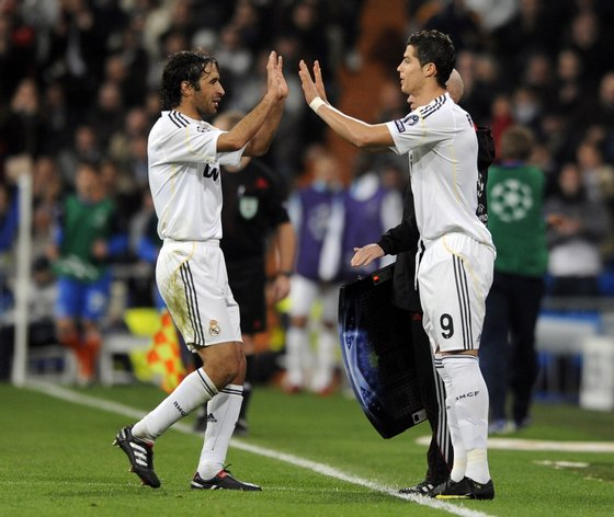 Real Madrid's Portuguese forward Cristiano Ronaldo (R) replaces Real Madrid's captain Raul Gonzalez (L) during a Champions league group C football match at Santiago Bernabeu stadium in Madrid on November 25, 2009. AFP PHOTO/JAVIER SORIANO. (Photo credit should read JAVIER SORIANO/AFP/Getty Images)