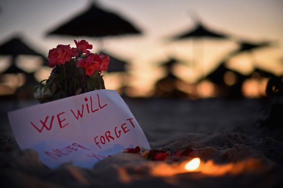 SOUSSE, TUNISIA - JUNE 28: A candle and flowers are left at Marhaba beach near to where 38 people were killed on Friday in a terrorist attack on June 28, 2015 in Souuse, Tunisia. Sousse beaches remain quiet following the Tunisia beach attack which left 38 dead, including at least 15 Britons while numerous tourists returned to the UK with more set to follow in the coming days. (Photo by Jeff J Mitchell/Getty Images)